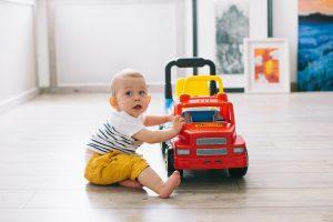 niemowlę siedzi obok jeździka w kształcie samochodu
