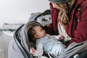 matka wkłada dziecko do wózka z daszkiem